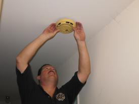Gamber & Community Fire Co. firefighter and Public Information Officer, Bruce Bouch, inspects an old smoke alarm. This existing alarm was discovered to be dated August 1981.
