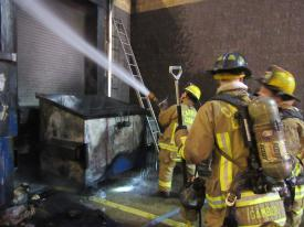 Firefighters work to extinguish remaining hot spots in the ceiling of the loading dock.