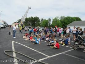 Families listen to Public Information Officer Bruce Bouch as he introduces the Side-By-Side demonstration. Sykesville Fire Department's Tower 12 is in the background.