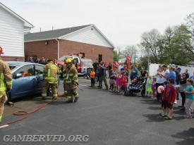 "Families watched as firefighters removed the windshield and doors of a Toyota Prius to rescue the ""victim"" inside during this training scenario."