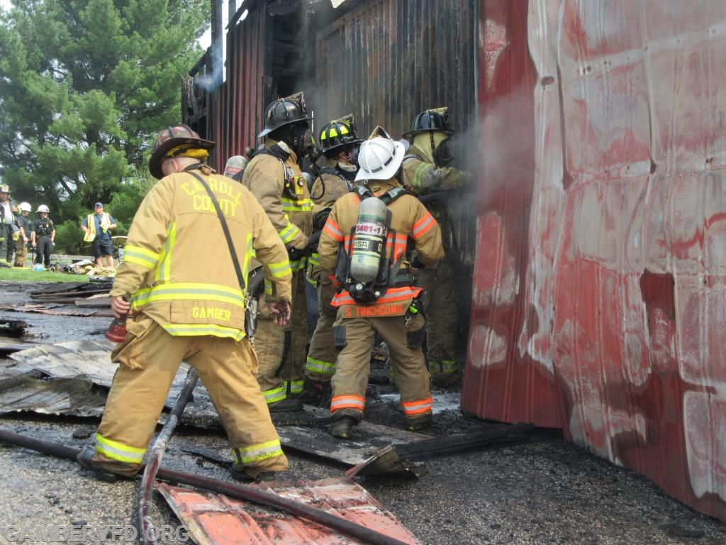 Firefighters apply foam to the inside of the sea container.