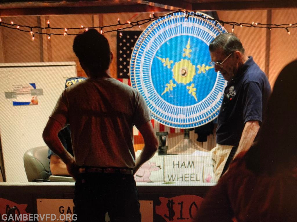 Charlie running the ham wheel at the carnival.
